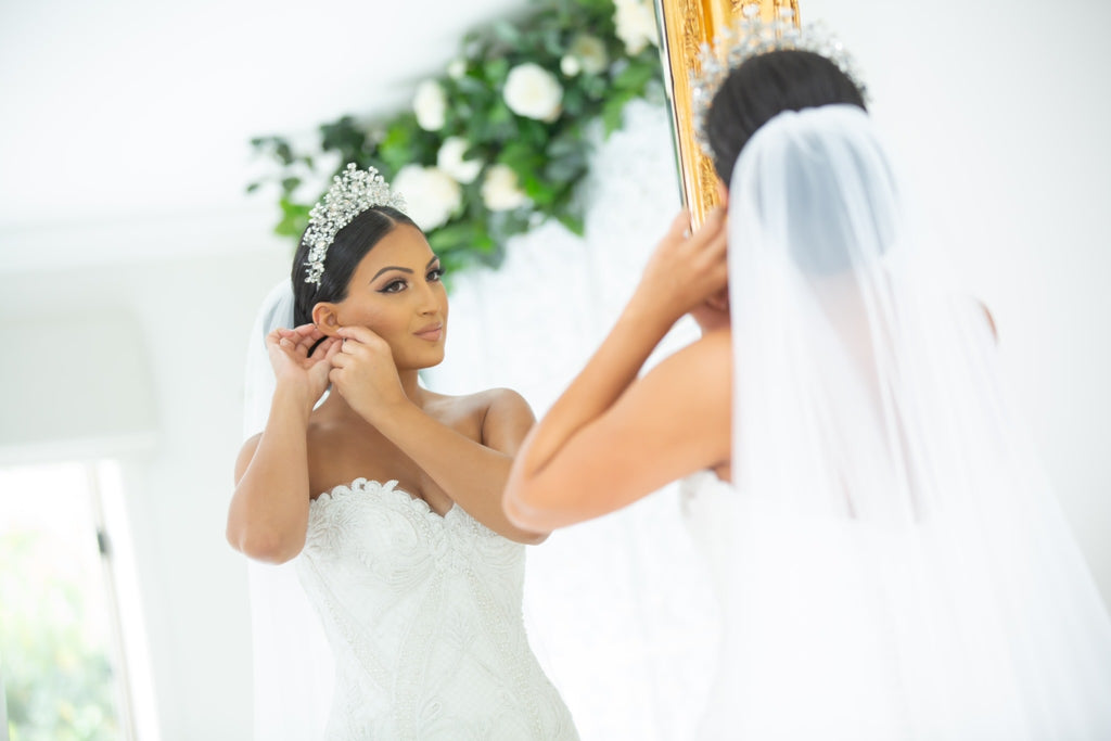 Georgette wearing our Katrina Bridal Crown putting on earrings in the mirror