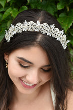 Load image into Gallery viewer, Smiling Bride wears a low tiara with crystals in pale gold. She has dark hair and green leaves behind her.
