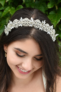 Smiling Bride wears a low tiara with crystals in pale gold. She has dark hair and green leaves behind her.