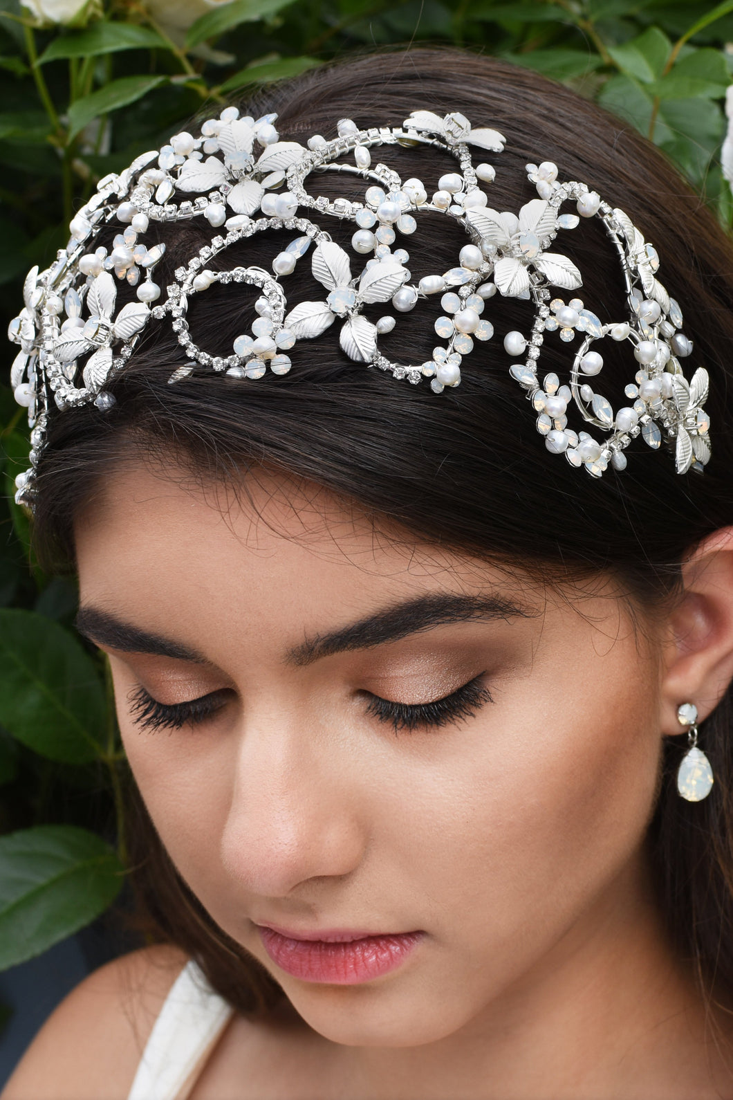 Dark haired model wears a very wide silver headband on the front of her head with green leaves as a background