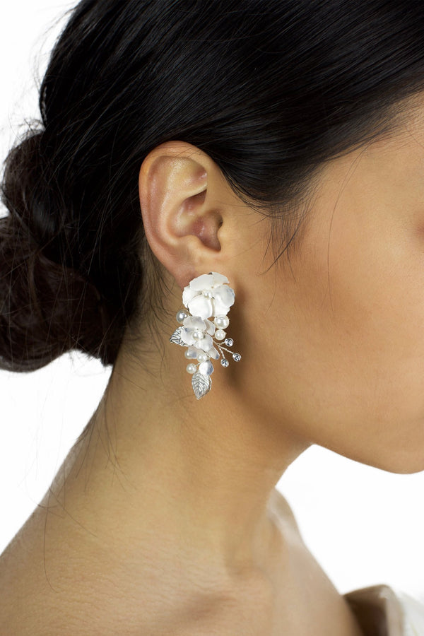 Silver hand painted earrings with pearls worn by a dark haired model bride