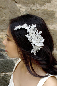 White lace bridal side comb with pearls worn by a bride in front of a stone wall