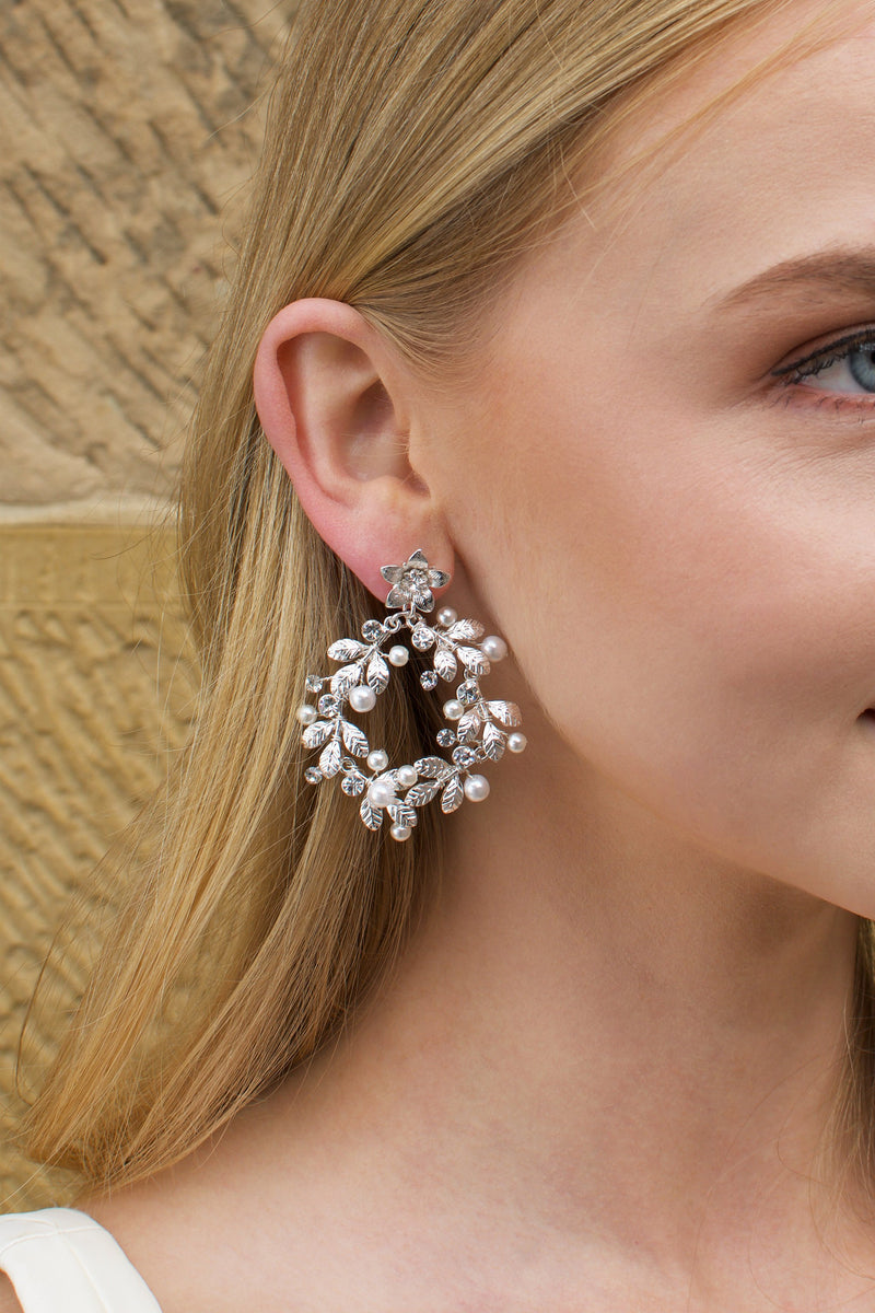 Model with Blonde hair wears a silver hoop shape earring in her ear.