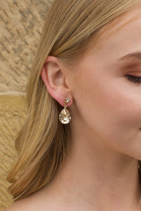 A blonde model wears a pale gold earring with a silk colour stone in her ear with a stone wall background