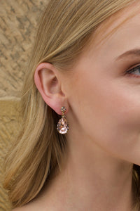 A blonde model wears a gold earring with a vintage rose colour stone with a sandstone wall background