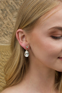 A blonde model wears a gold earring with a clear stone with a stone wall background