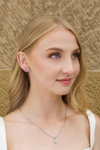 Model wears a silver chain pendant necklace with a single stone and a matching stud earring