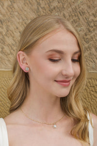 A blonde hair model wears a gold stud earring with a simple gold chain with a stone wall backdrop