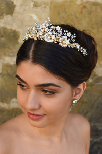 A dark haired model wears a gold tiara with pearl flowers against a stone wall background.