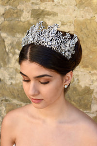 A Tall Bridal Tiara in Silver worn by a Dark Hair Bride with an old stone wall background