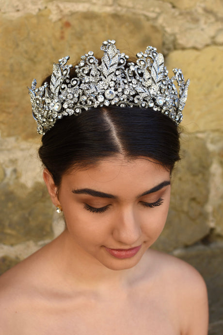 A high many points crown worn by a dark hair model with an old sandstone wall backdrop