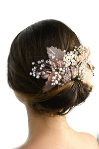 A model with brown hair wears a rose gold and filigree leaves Bridal Vine at the back of her head against a white background