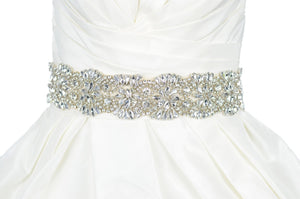 Wide crystal stones belt on ivory ribbon worn on an ivory bridal gown with white background
