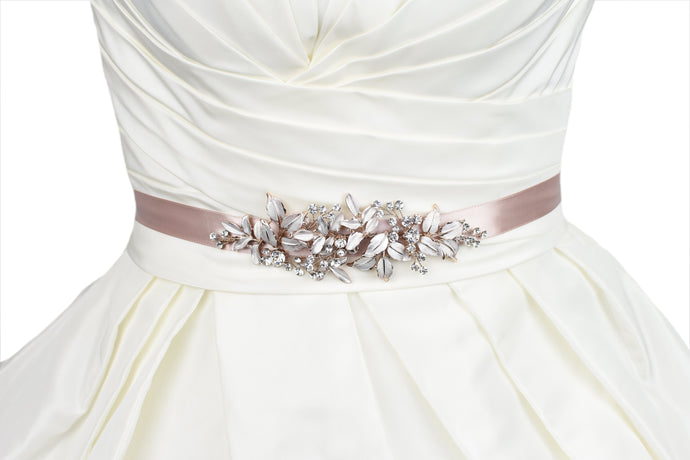A dark pink ribbon with rose gold leaves design is around the waist of an ivory bridal gown