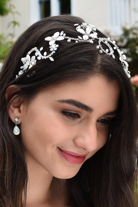 Dark Haired smiling model wears a silver bridal headband with white opal stones with a garden background
