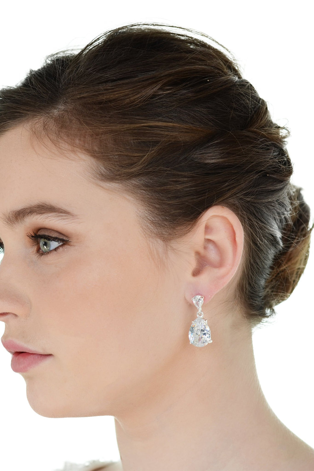 Dark haired model wearing a pear shaped stone earring against a white background.