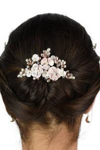 The back of  the head of a bride wearing a soft rose gold bridal comb in her dark hair