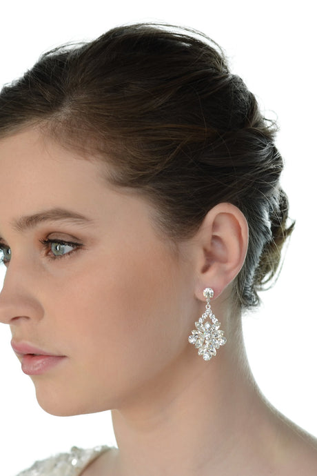 A dark haired model wears a wide drop earring with a white background