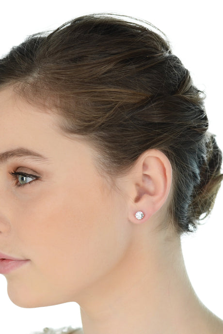 A model with green eyes and dark hair looks away wearing a simple stud earring
