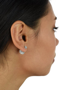 The ear of a dark hair model shows a large crystal ball at the back of the ear with a small crystal ball on the front of the ear.