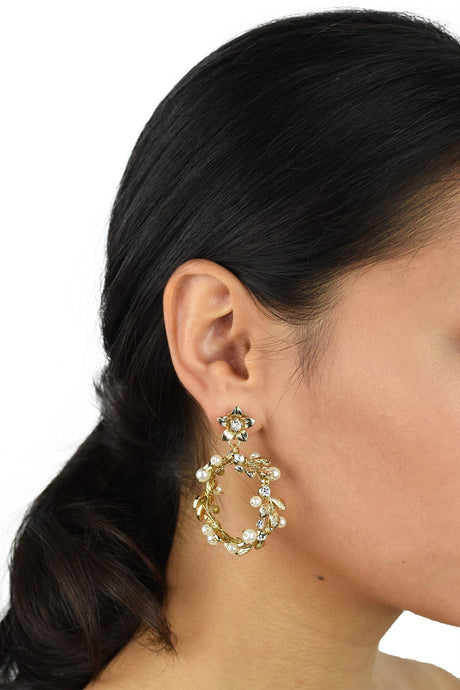Model wears a gold hoop shape earring. She has dark hair.
