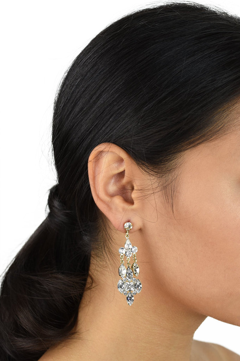 Dark haired Bride wearing a mid length silver drop earring with a post fitting on a white background.