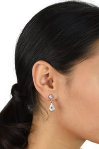 A model with black hair wears a rose gold teardrop earring in her ear against a white background