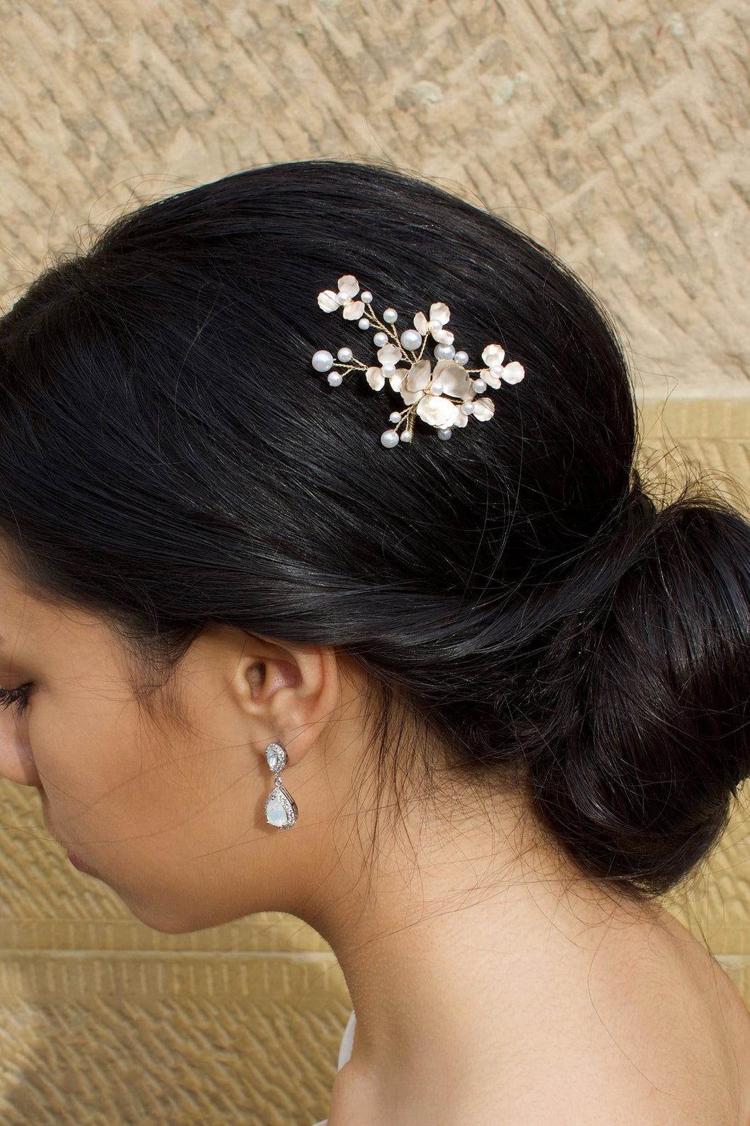 Dark hair model wearing a small gold and pearl hair pin with a stone wall behind