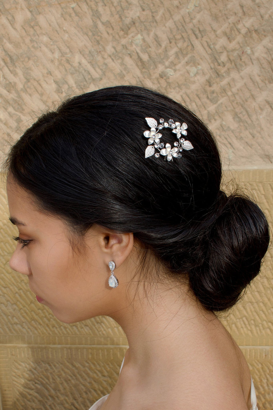 Ring of silver leaves and flowers hairpin worn by a dark hair bride on the side of the head with a sandstone background
