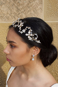 A side view of a model with dark hair wearing a gold bridal headband