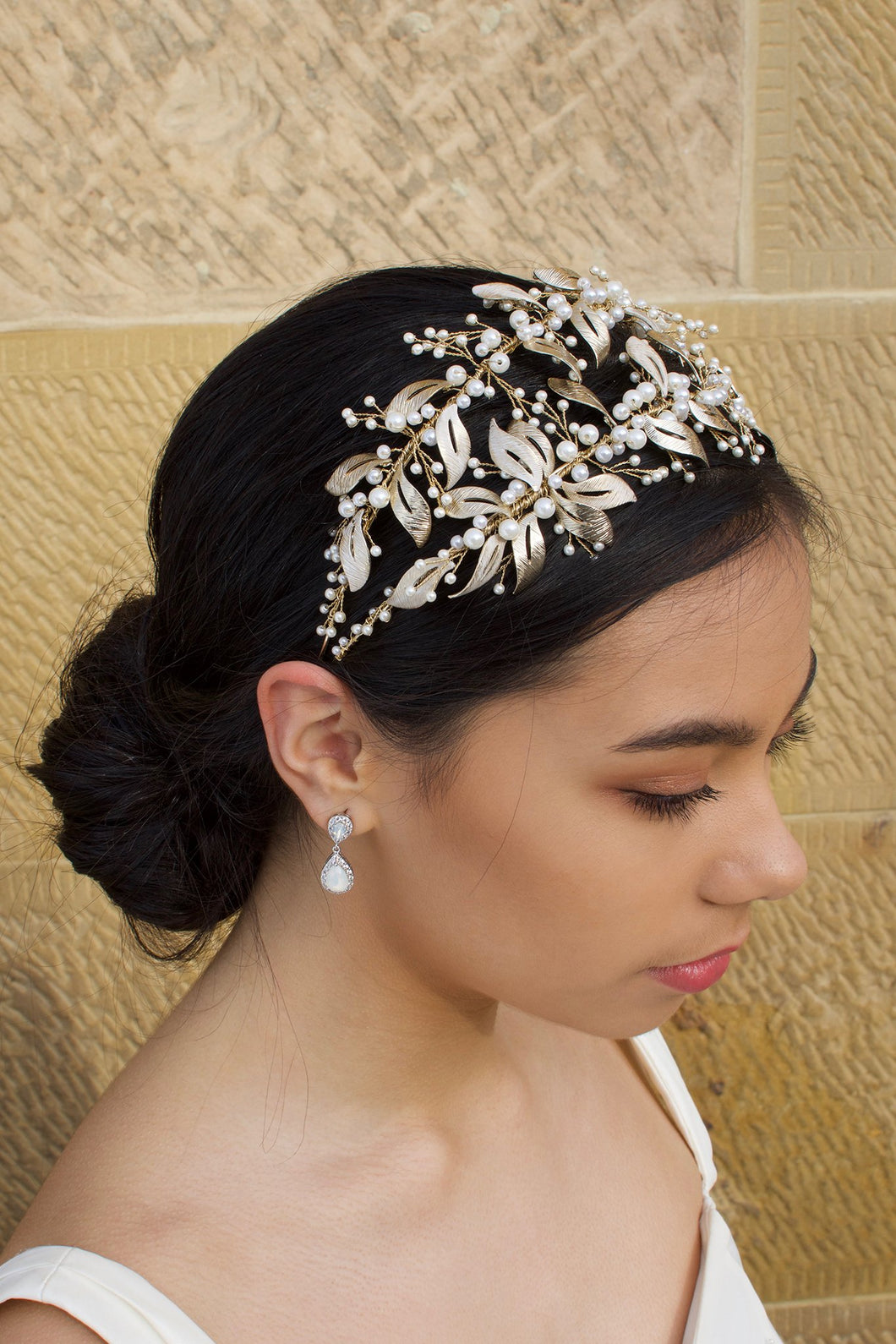 Double row pale gold headband with pearls worn by a dark hair model with a sandstone wall