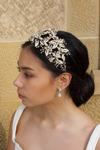 Side View of Double row pale gold headband with pearls worn by a dark hair model with a sandstone wall