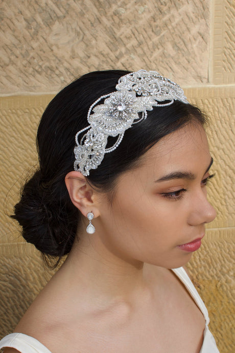 Seed Pearl wide headband worn by a black hair bridal model with a stone background