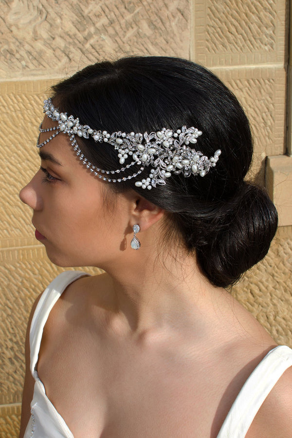 On the side of her head a bride wears a pearls and rhodium handmade vine with a stone wall backdrop