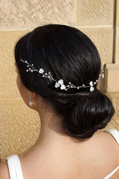 Thin wire bridal vine with pearls and small flowers on a black hair bride pictured in front of a stone wall
