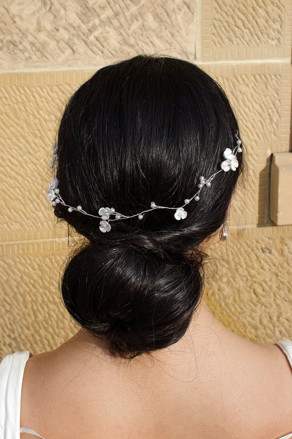 Single Strand Silver wire pearl vine worn at the back of a brides head shown with a stone wall behind