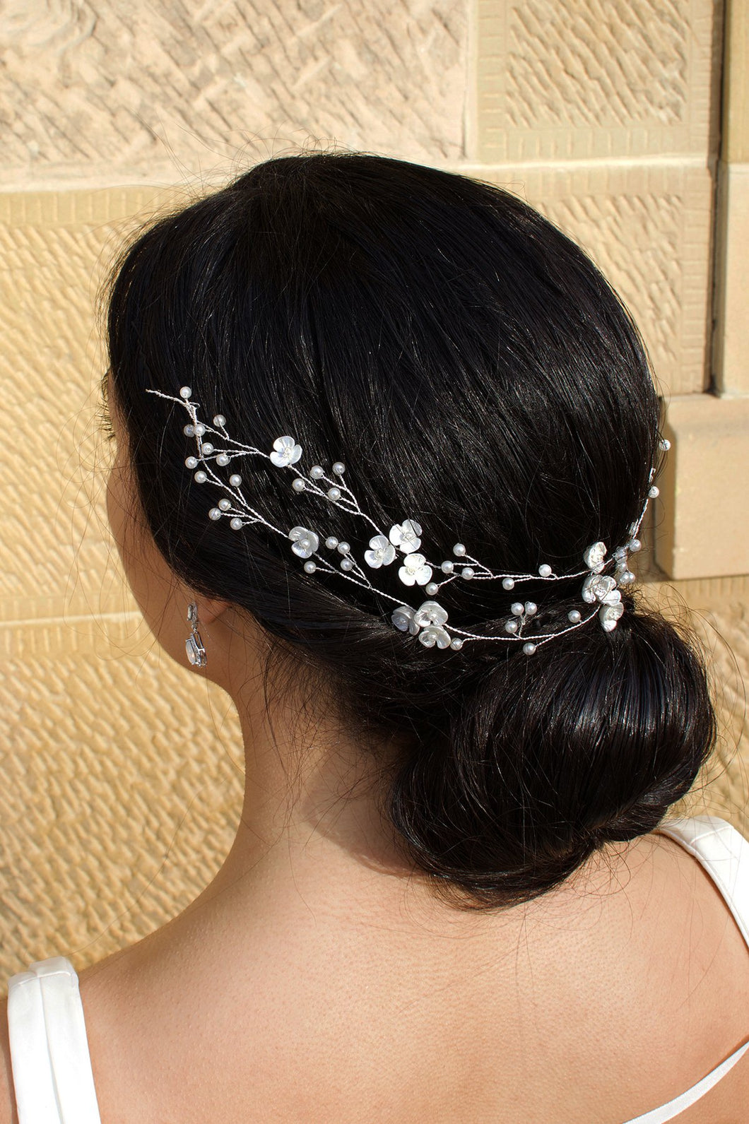 Double row silver and pearl vine on a dark haired model with a stone wall backdrop