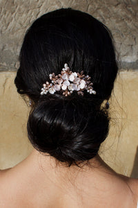 A black hair model wearing a pale rose gold comb above a bun of hair
