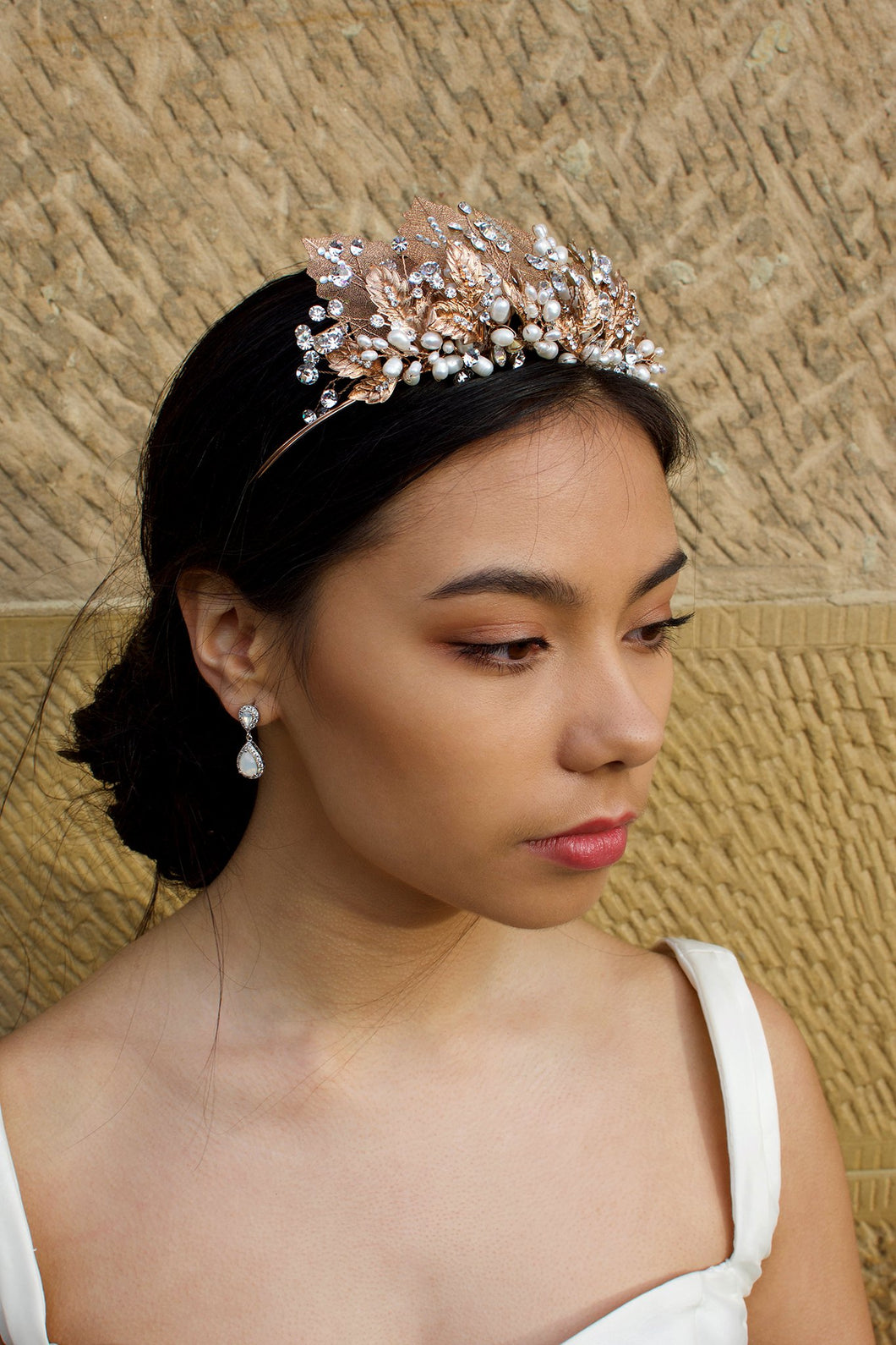 A black haired model wears a rose gold tiara with pearls in the background is a  wall.