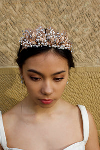A black haired model wears a rose gold tiara with pearls in the background is a sandstone wall.