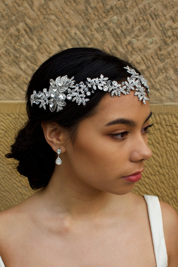 Dark Silver vine of leaves encrusted with tiny crystals worn across the forehead of a dark haired bride with a stone wall behind