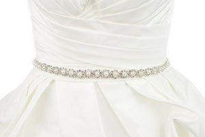 A narrow pearl bridal belt with rings of crystals around the pearls is worn on an ivory bridal gown