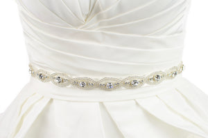 A thin crystal and beads bridal belt is worn on the waist of an ivory bridal gown