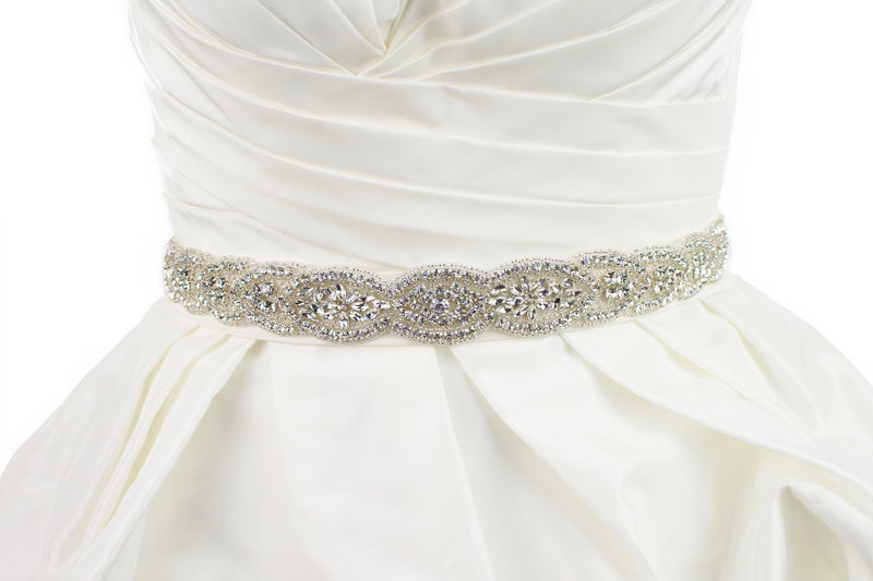 Silver Bridal belt full of shining stones worn on an ivory bridal gown with a white background