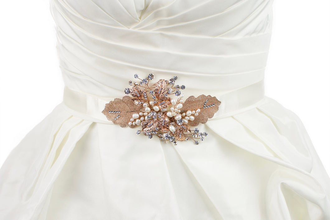 Rose Gold Leaves Motif on an ivory satin ribbon worn on an ivory satin bridal gown