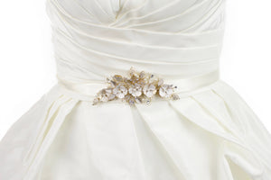 Soft pale gold flowers on an ivory satin bridal belt worn on an ivory bridal gown