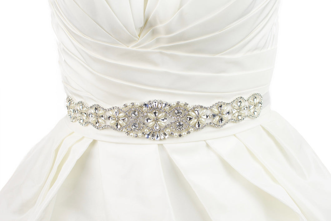 belt on a bridal dress with crystals and pearls on an ivory ribbon on an ivory bridal gown