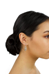 A short drop earring in gold is worn by a dark hair bridal model with a white background