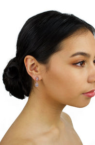 Small pear shape rose gold earring worn by a bridal model with dark hair on a white background