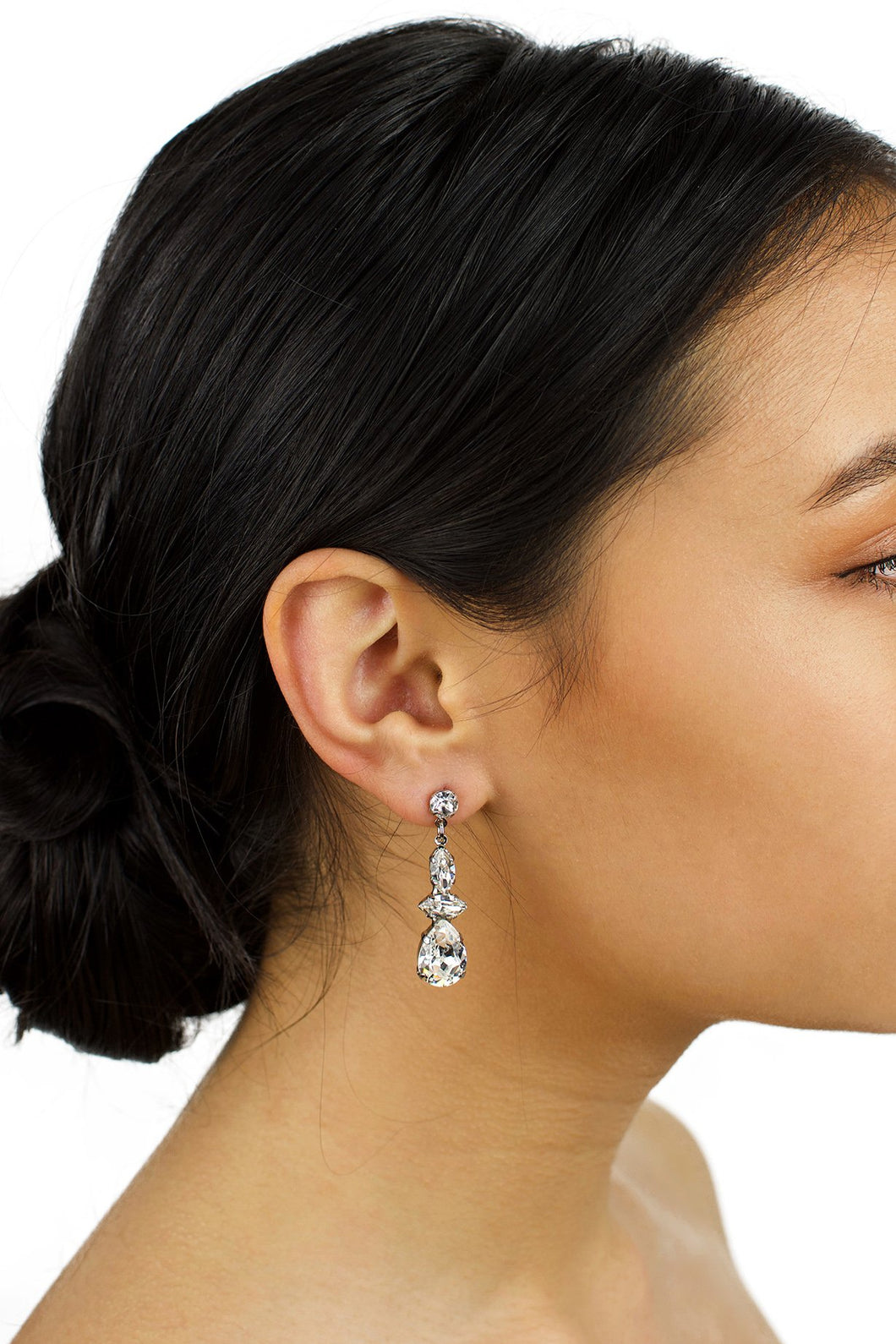 Dark hair model wearing a short Swarovski Crystal drop earring with a white background